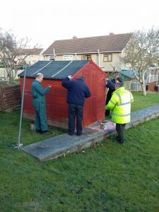 A photo of people building a shed